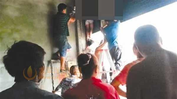 村民们正在救两名被卡在卷帘门里的孩子